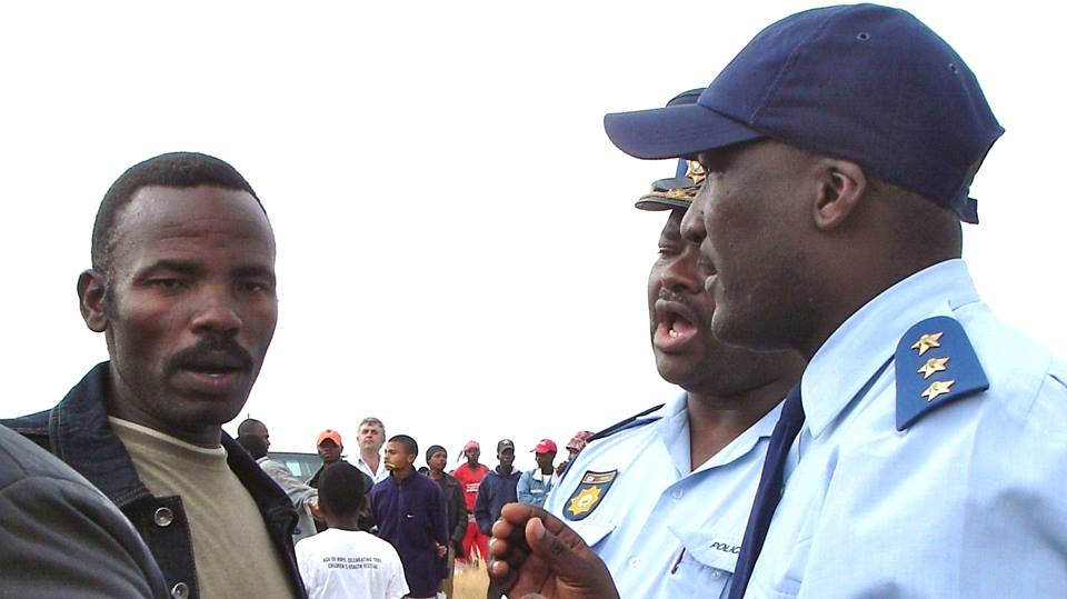 Bazooka, negotiating with SAPS officers to keep the peace at Xolobeni JSS in August 2008, when Minister Buyelwa Sonjica addressed a rally to announce the award of mining rights. She subsequently apologised and suspended the rights. Photo: John Clarke